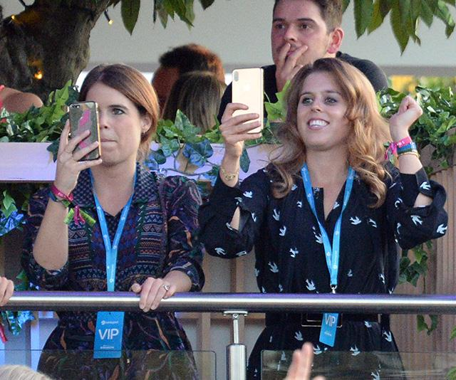 Getting content! Both Eugenie and Beatrice were spotted filming parts of the concert on their smartphones.