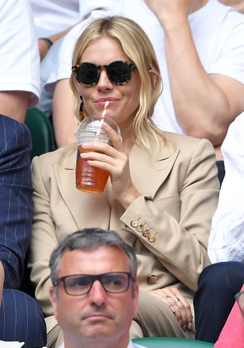 The ever-classy Brit enjoyed a refreshment as she watched the action unfold from the stands.