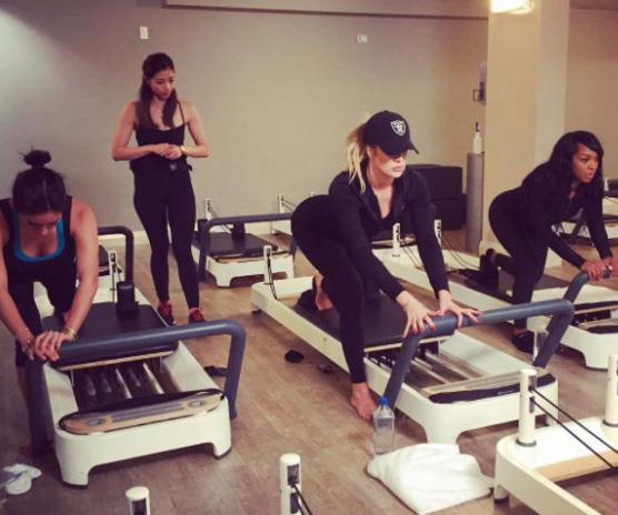 Khloe Kardashian doing a group reformer Pilates class with her girlfriends.