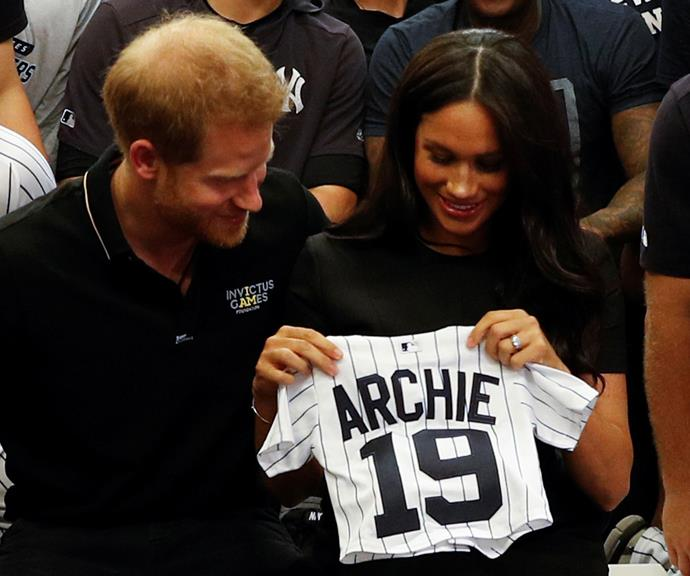 Harry and Meghan were gifted an adorable onesie for baby Archie at a recent public appearance at the baseball.