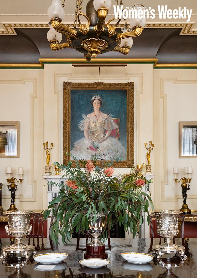 The dining room table, set with native Australian flowers, below Augustus John's painting of HM Queen Elizabeth.