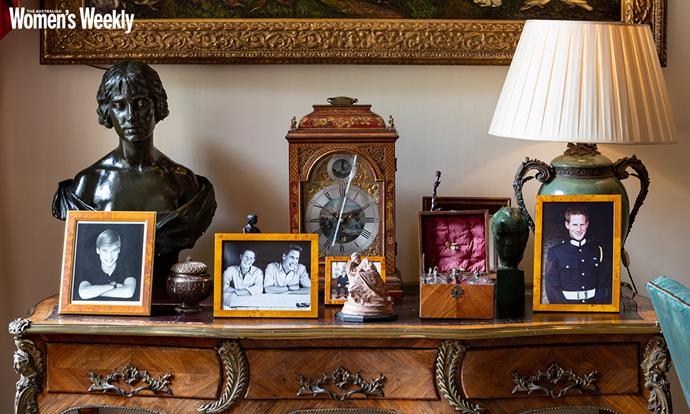 A bronzed plaster bust of the Queen as the Duchess of York, by Louis Frederick Roslyn, sits with treasured photos of Princes William and Harry as young men and an ornate clock.