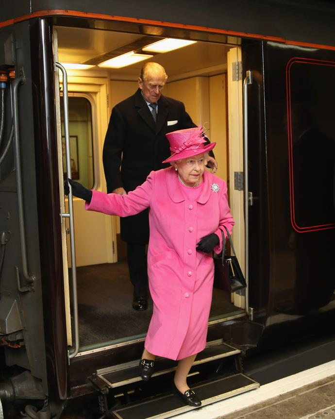 The Queen often travels by train, seen here on the official royal train with Prince Philip.