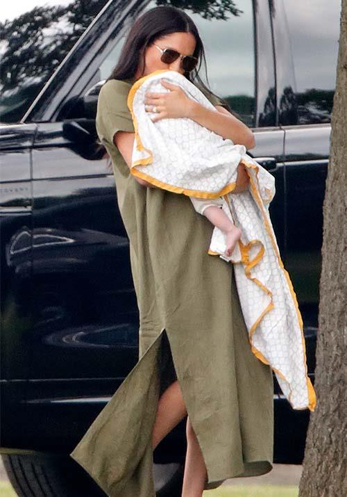 "In a surprise appearance, Meghan [stepped out at the polo](https://www.nowtolove.com.au/fashion/fashion-news/meghan-markle-kate-middleton-polo-dresses-56978|target=""_blank"") on July 10 wearing this ultra chic olive green caftan dress by Lisa Marie Fernandez. The dressed-down look on Megs was a glorious sight - we don't usually get to see the new mum channel her LA cool-girl style!"