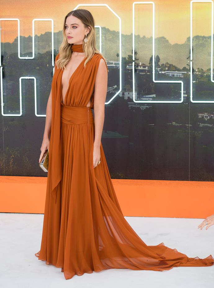We thought we'd seen the best, but Margot has only gone and *slayed* the fashion stakes once again at the UK premiere of *Once Upon a Time in Hollywood* in July 2019. The Aussie actress looked phenomenal in this stunning burnt orange number featuring a scarf and a daring plunging neckline.