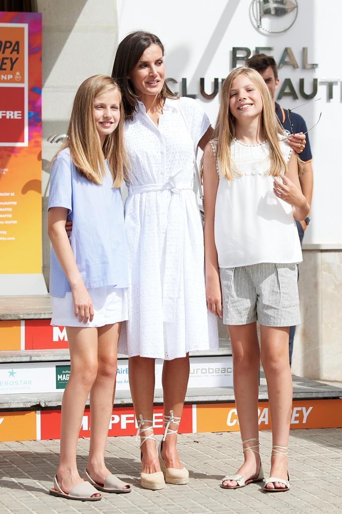 They're definitely glowing! Stepping out at the 38th Copa del Rey (King's cup) regatta, Letizia's white dress and wedge espadrilles are a peak summer mood. And how chic do her fashionable mini-me daughters look...
