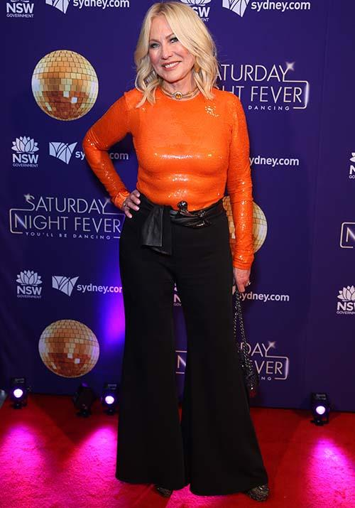 In April, KAK went big and did *not* go home in this sequined orange skin-tight top while attending a red carpet event for *Saturday Night Fever*. Talk about making a statement!