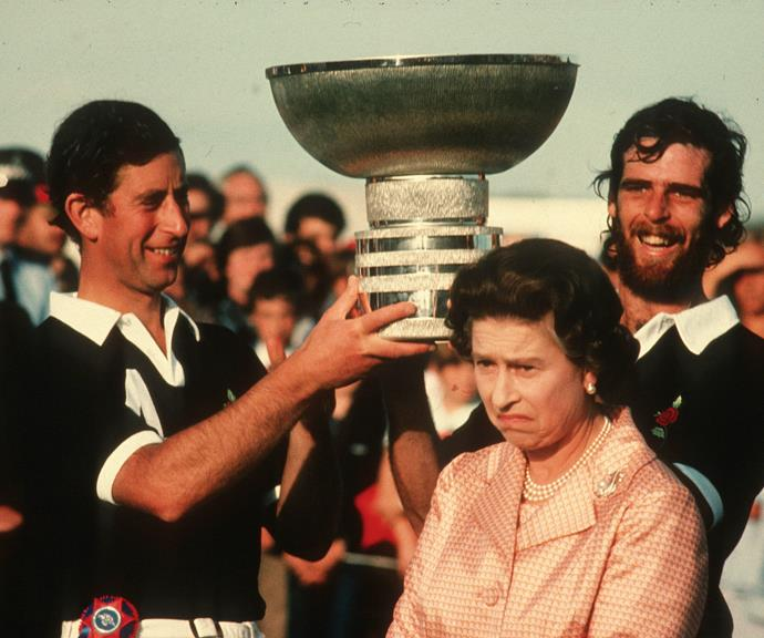 The Queen pulls a face as her son Prince Charles holds a trophy above her head following a polo match at Windsor Great Park in 1984.