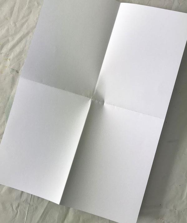 **STEP 1:** Fold A4 paper into half and half again; open up the sheet of paper. stamp in bottom right hand corner.