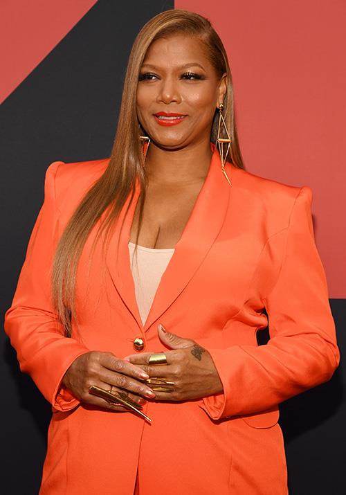 Queen Latifah is glowing in zesty orange.