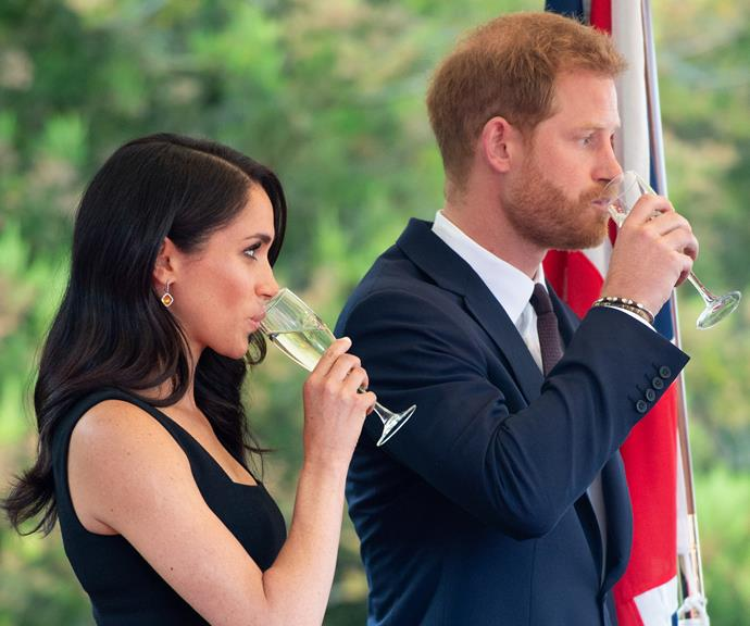Harry and Meghan sip on Champagne at a Summer Party at the British Ambassador's residence at Glencairn House in Dublin in July 2018.