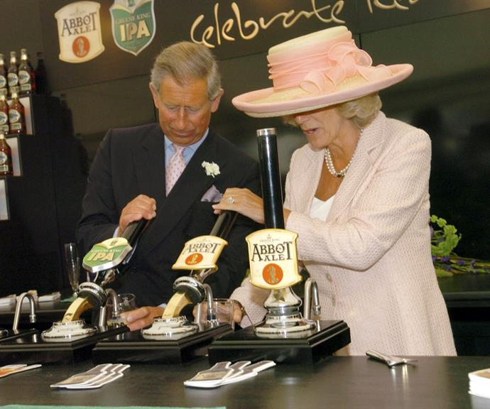 Prince Charles and Duchess Camilla pulling beers at a pub during an official royal engagement.