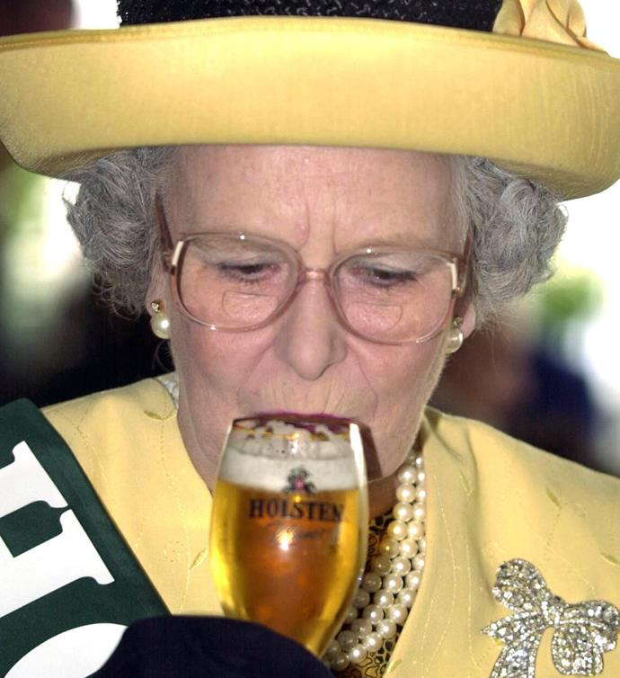 Cheers, Your Majesty! The Queen tucks into a beer.
