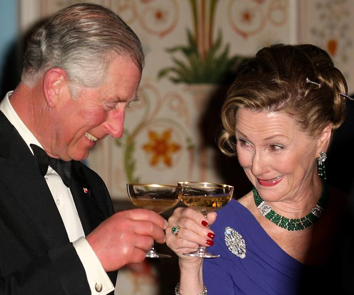 The charming Prince of Wales clinks glasses with a female guest at an official royal function.