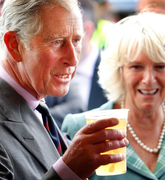 Prince Charles drinks at an official royal event while Duchess Camilla looks on.