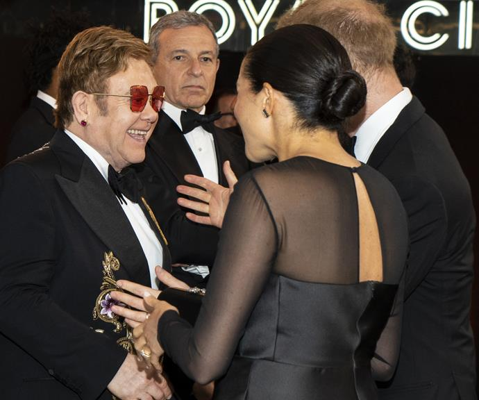 Elton John and Duchess Meghan share a laugh at *The Lion King* premiere in London.