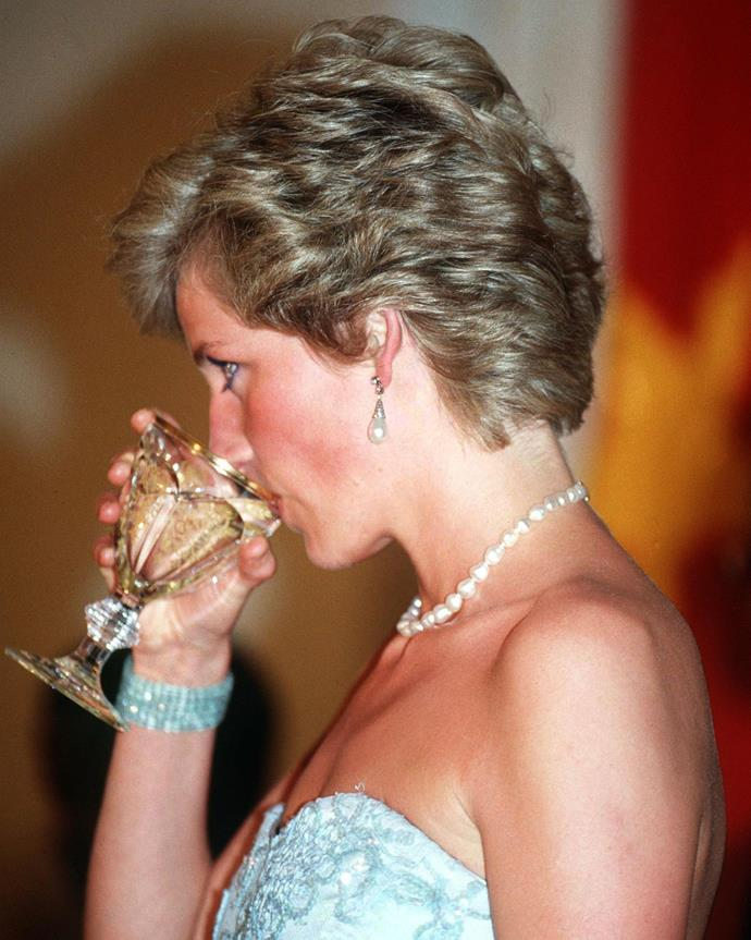 Princess Diana enjoying a drink at a presidential banquet held in Douala, Cameroon in 1990.