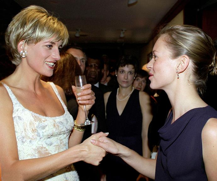 Princess Diana holds her drink while she shakes hands with Kate Moss at an event in New York in 1997.