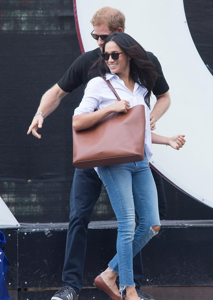 During her first official public outing with Harry in 2017, Meghan nailed her off-duty look with a simple white shirt, subtly-ripped jeans and matching brown leather bag and shoes.