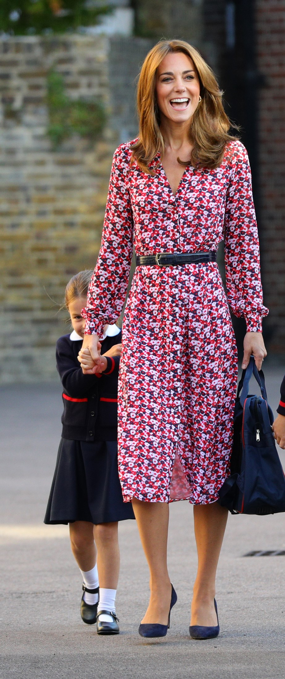 Charlotte was initially shy as she headed to class, hiding behind mum Kate. *(Image: Getty)*
