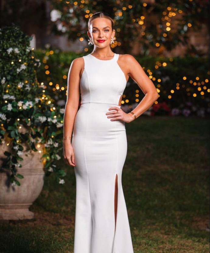 Her antics may not be considered pure, but Abbie looks heavenly in this floor-length white dress with a bold red lip and statement earrings.