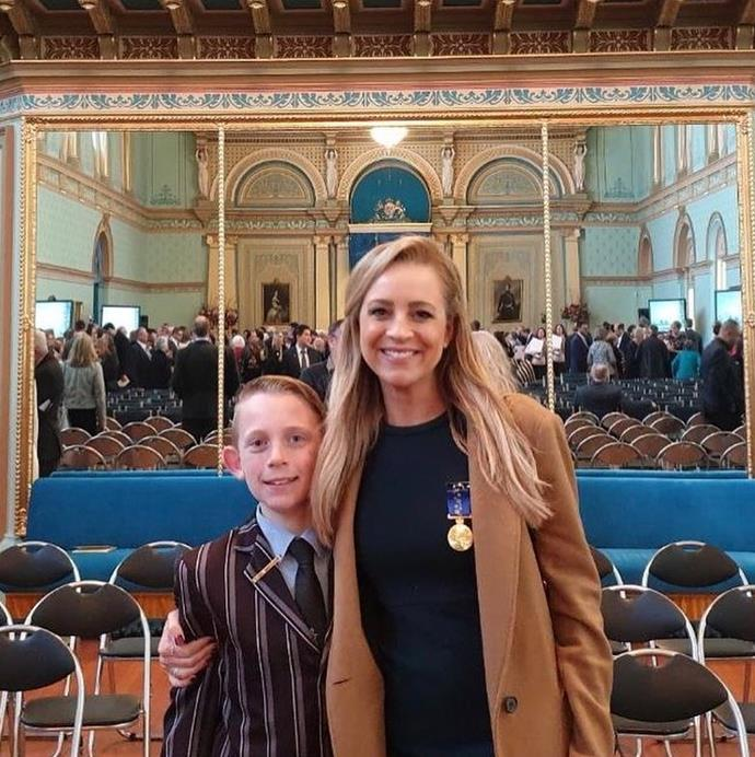 Looking sharp: Carrie smiles with her eldest son Ollie.