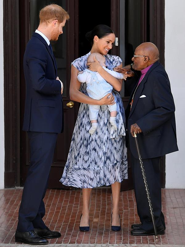 What does one wear for tea with Archbishop Desmond Tutu? Well if you're Duchess Meghan you opt for a sheer Club Monaco patterened dress with navy heels and her long locks tied back in a bun.