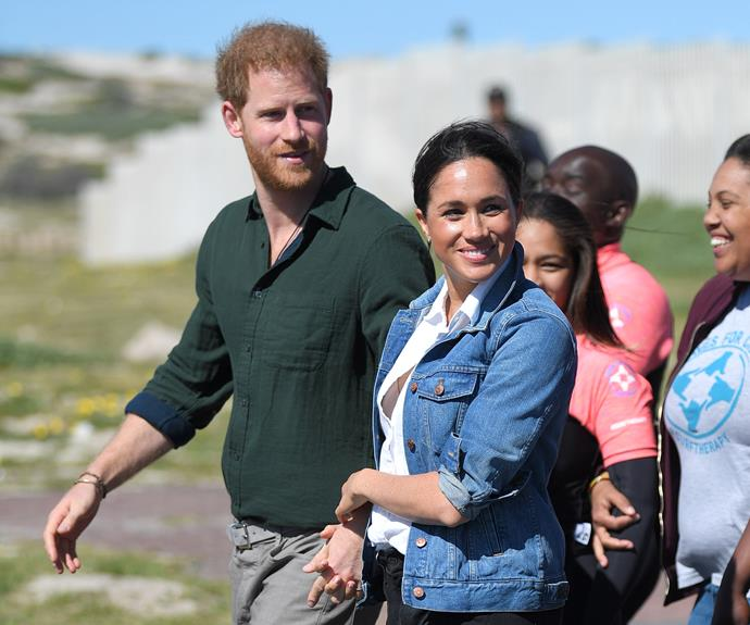 Meghan clutches onto Harry's hand on day two of the tour.