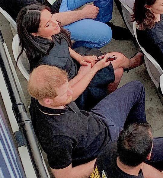 A sneaky Twitter user captured Harry and Meghan holding hands at the baseball, hidden away in the stands.