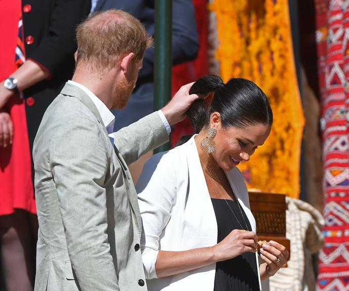 Harry helped Meghan adjust her ponytail while they were in Morocco, making sure it didn't get caught in her necklace.