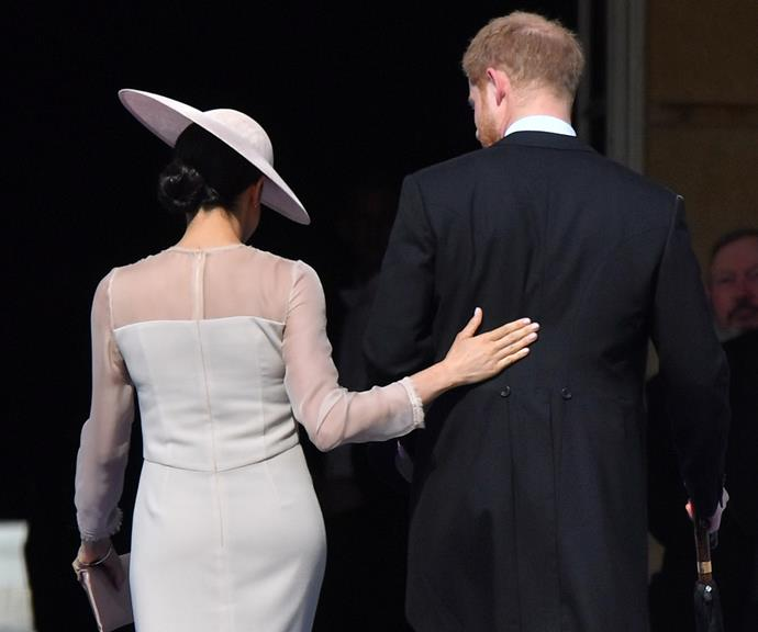 During their first official royal engagement after getting married, Meghan laid a protective hand on Harry's back.