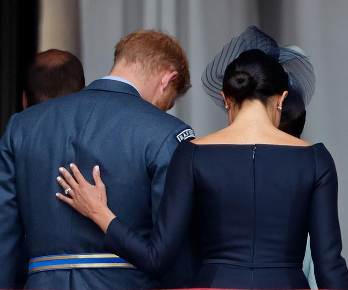 Meghan puts a protective hand on Harry's back after the Trooping The Colour ceremony.