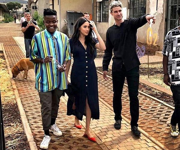At an engagement at Victoria Yards in Johannesburg, Duchess Meghan's navy blue shirt dress was effortlessly fashionable, but that pop of colour from her red ballet flats is just perfect!