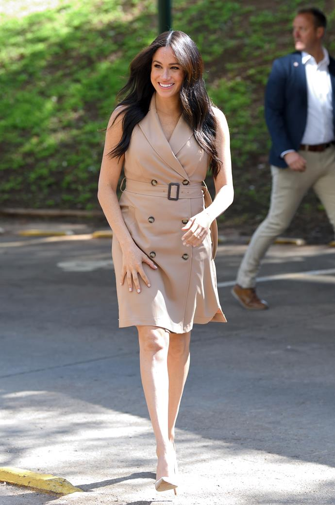 Duchess Meghan joined students and educators at The University of Johannesburg dressed in a nude trench dress from Banana Republic with Stuart Weitzman heels and a delicate bracelet by Alemdara.