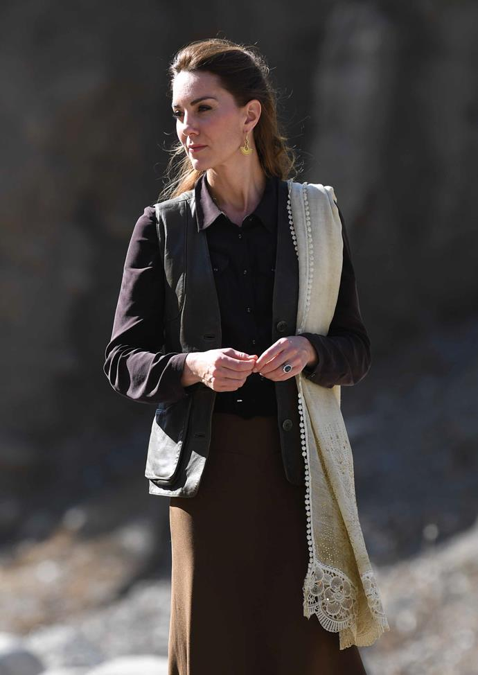 Kate's earthy-toned ensemble consisted of a sleeveless waistcoat designed by Really Wild, a recycled look on the Duchess who previously wore the style on her royal tour of India and Bhutan. Kate also wore her Really Wild boots, pairing them with a brown skirt and shirt.  She finished her look with a stunning pair of golden drop earrings.