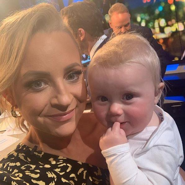 Carrie poses with baby Adelaide on The Project desk.