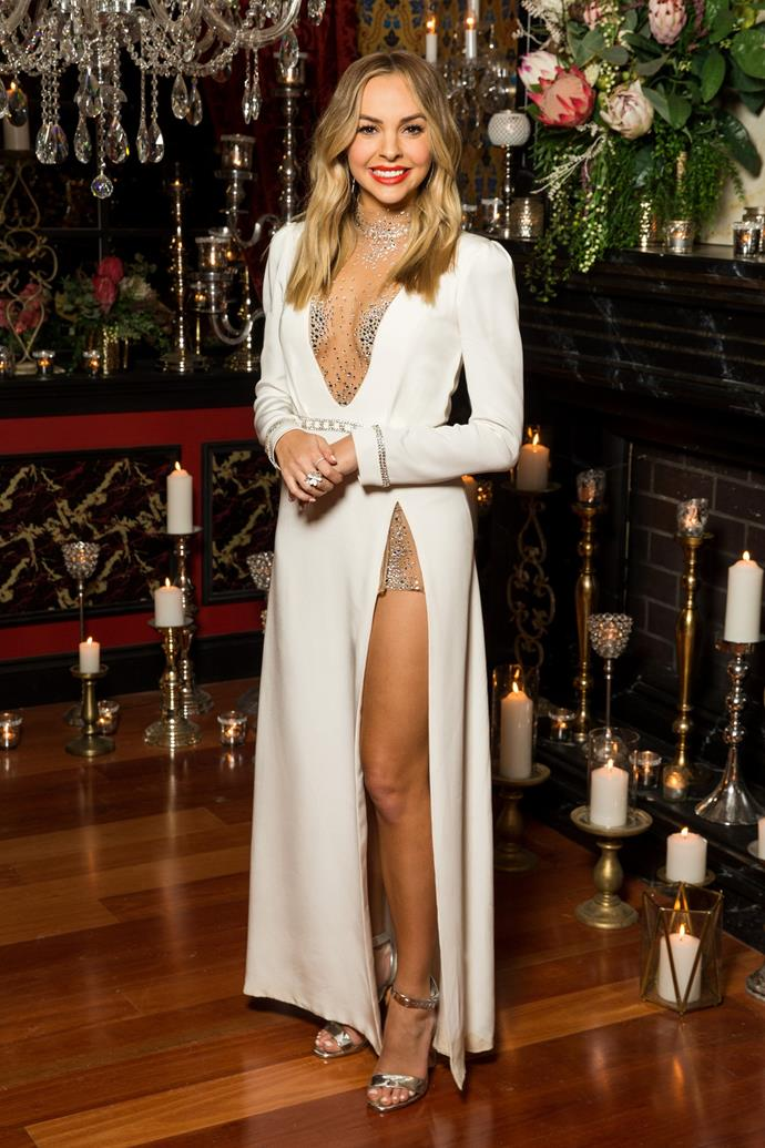 "In the [premiere episode](https://www.nowtolove.com.au/reality-tv/the-bachelorette-australia/bachelorette-24-hour-rose-carlin-59632|target=""_blank""), Angie looked every bit the ultimate catch of the century, wearing this beautiful long-sleeved Klovia Couture gown, which featured a bejewelled sheer V-neck and thigh-high split. Babe town!"
