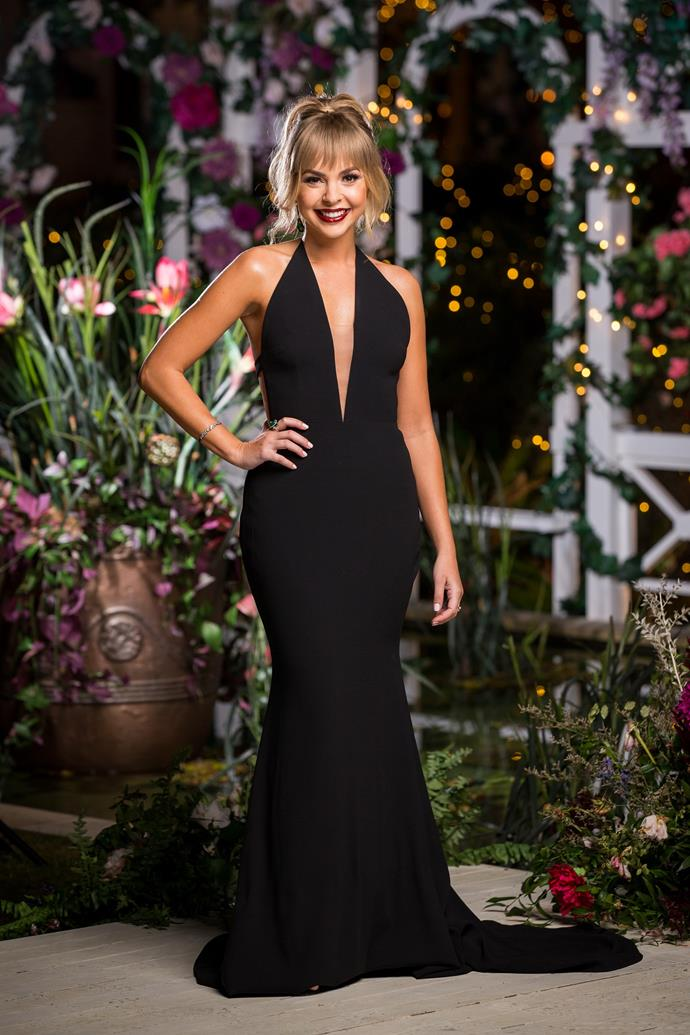 "On episode three, Angie [upped the ante](https://www.nowtolove.com.au/reality-tv/the-bachelorette-australia/yvie-jones-bachelorette-2019-59808|target=""_blank"") in this classy black Alex Perry cocktail dress featuring a deep V-neckline and train, while wearing her hair in a chic up-do with a cute fringe. This is one of our favourite looks on the *Bachelorette* beauty to date."
