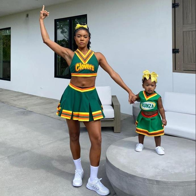 """Brought It. #CaliforniaLove."" Gabrielle Union recreated her *Bring it On* East Compton Clovers character longside her 11-month-old daughter, Kaavia."