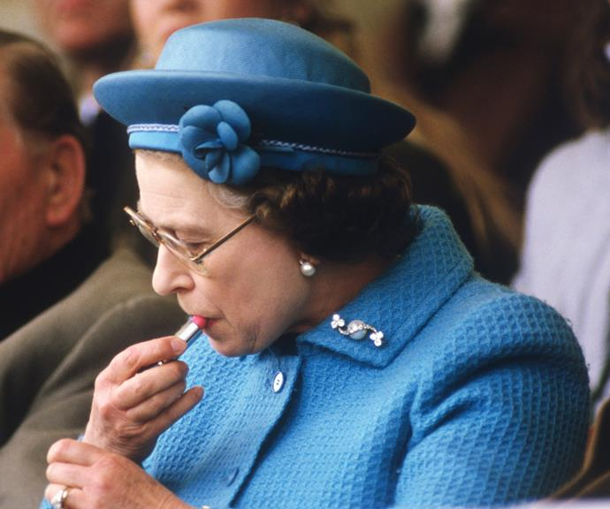 The Queen applies her own makeup at an official event.