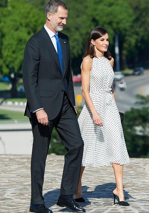 "In one of her very first looks, the [stunning Queen](https://www.nowtolove.com.au/royals/international-royals/queen-letizia-pink-dress-57001|target=""_blank"") looked incredible in a sleeveless polka-dot midi dress, which featured a flowing hemline and tie at the waist."