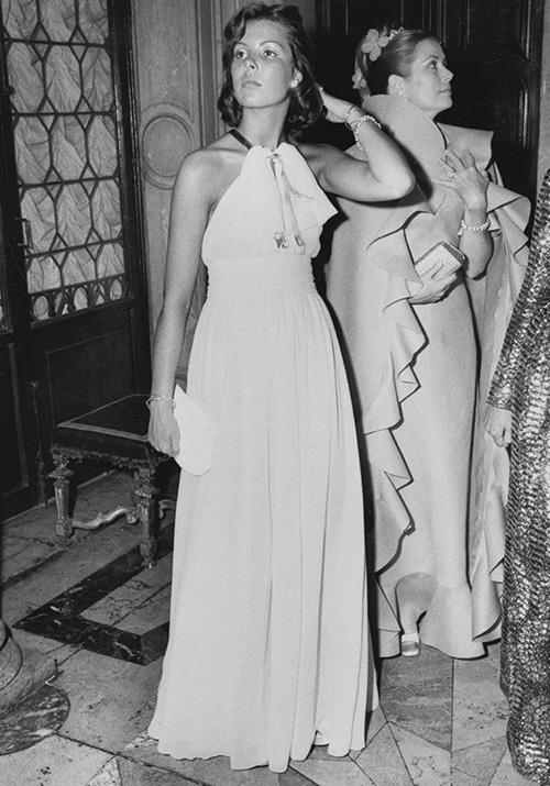 In 1973, Caroline attended the Volpi Ball in Venice alongside her mum Grace Kelly (pictured in the background). We're obsessed with her drawstring floaty gown.