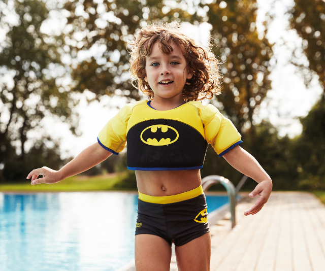 **Warner Bros. x Zoggs Waterwings Swim Vest:** Up, up and away with these gorgeous superhero-themed swim vests. Have peace of mind knowing that your child has the buoyancy assistance they need in the water, without the movement restrictions that you find with some other swim aides. Available at most major retailers.