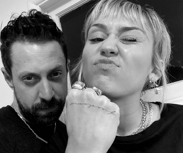 Miley showing off her new ink alongside her tattoo artist.
