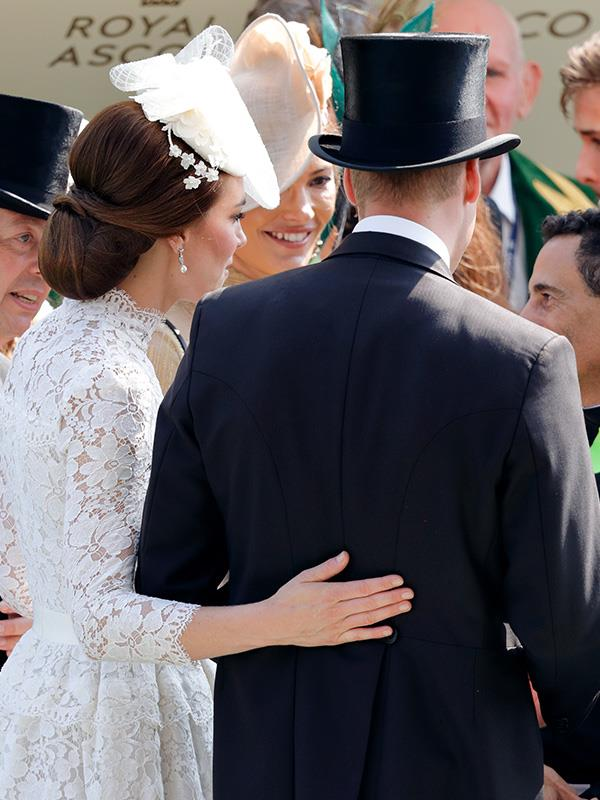 This time, it was Kate's turn to place a protective hand on William's back.