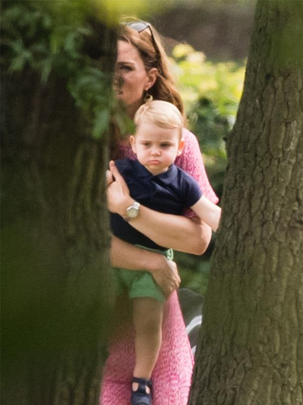 An adorable Prince Louis wriggles in his mother's arms at a polo match.