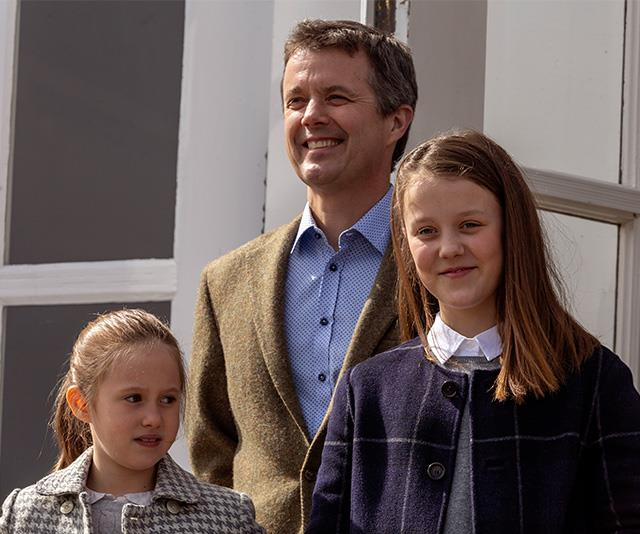 Frederik stands proudly with his two daughters.