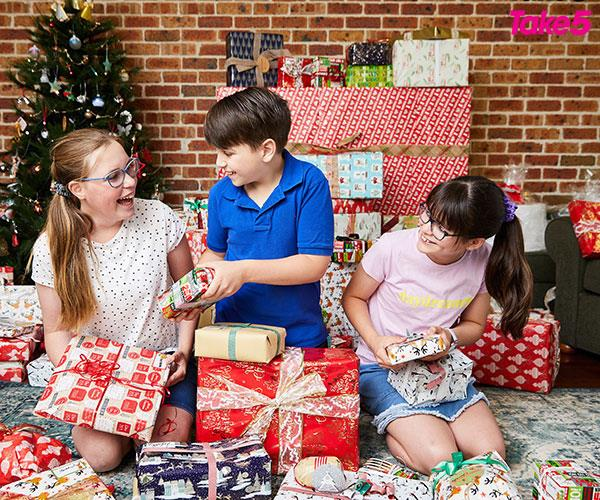 Maddison, Thomas and Charlotte trying to guess what's inside the wrapping.