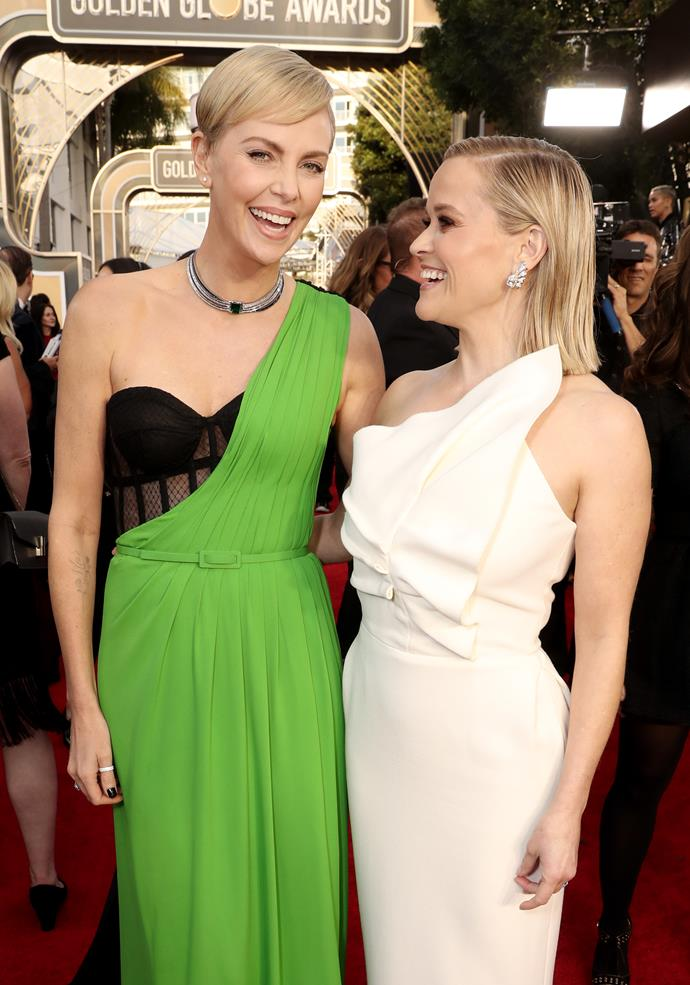 Charlize Theron & Reese Witherspoon share a sweet moment on the red carpet. We're intrigued by Charlize's bold green look, too!