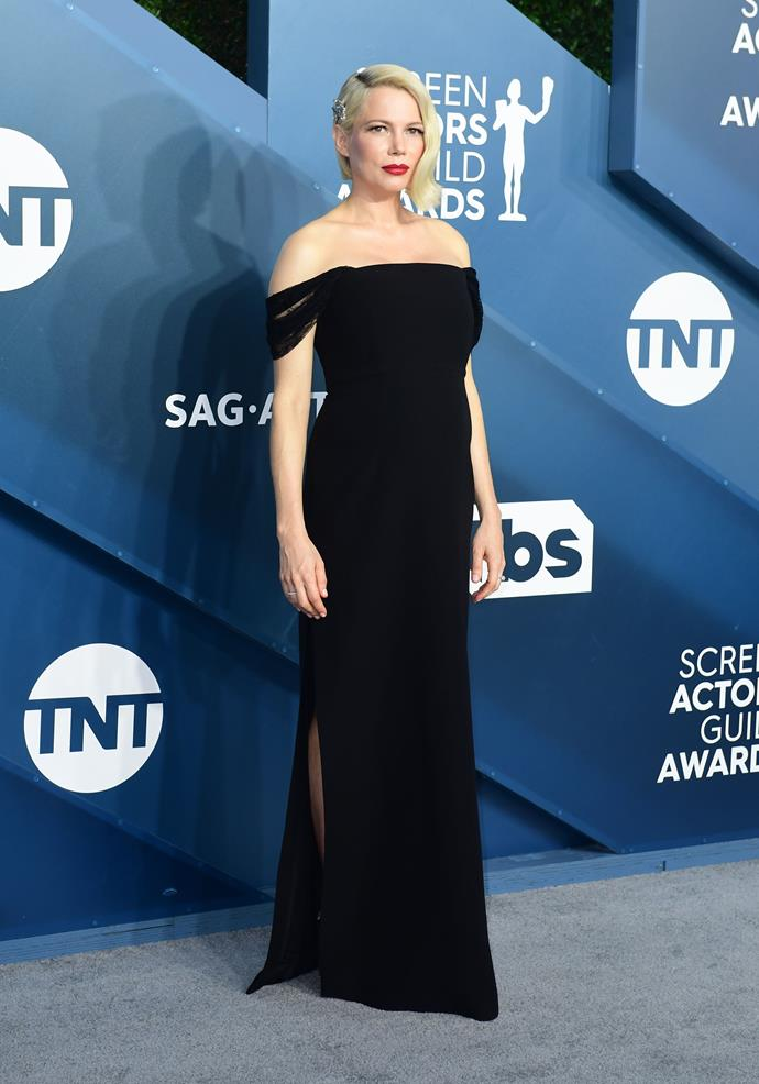 Michelle Williams rocks a bold lip to brighten up her dark ensemble.